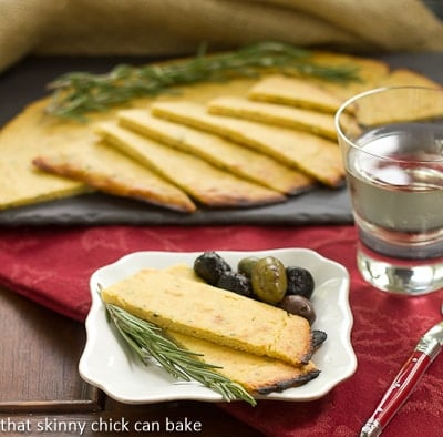 Socca from Vieux Nice sliced on a plate with rosemary and olives