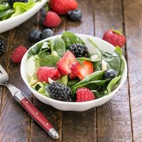 Spinach berry salad in a small white bowl with a red handled fork
