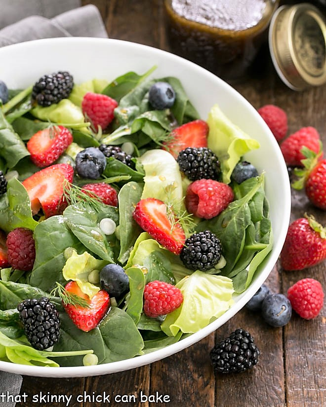 Spinach berry salad in a white ceramic bowl surrounded by fresh berries