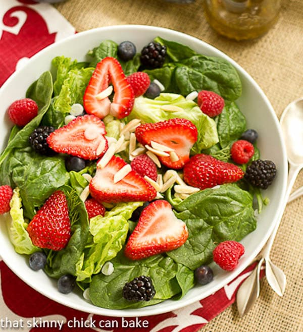 Overhead view of Spinach Almond and Berries Salad in a white bowl
