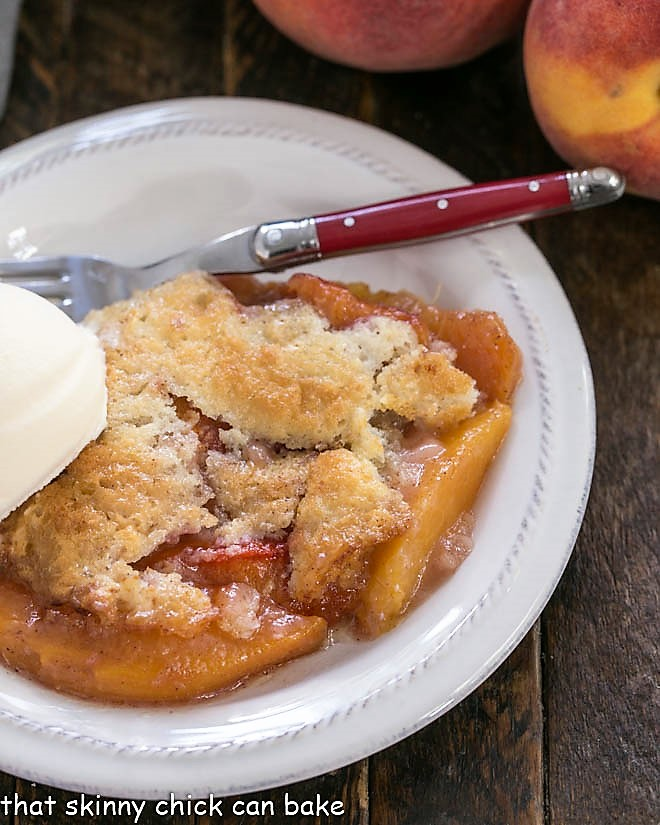 Peach Cobbler on a white dessert plate topped with a scoop of vanilla ice cream