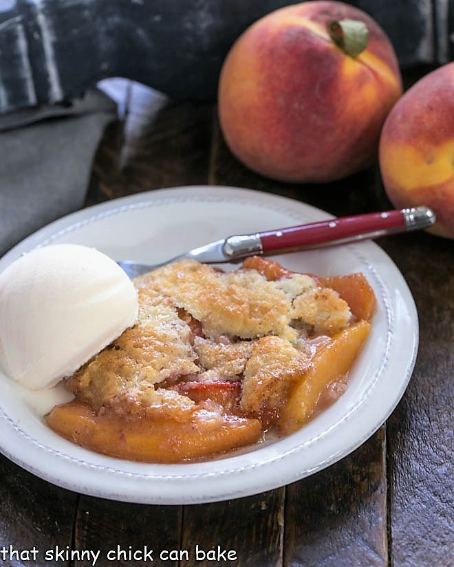 Easy peach cobbler on a white plate with scoop of vanilla ice cream with two fresh peaches in the background