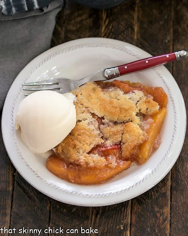 Overhead view of an easy peach cobbler topped with a scoop of vanilla ice cream with a red handled fork