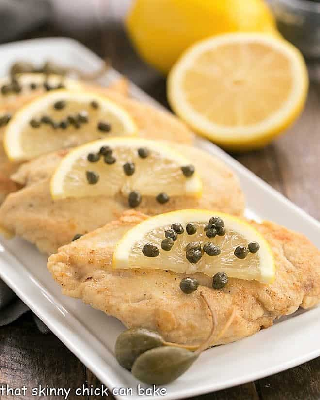 Easy Skillet Chicken Piccata on a white tray with lemon slices and capers