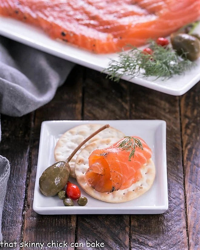 A slice of gravlax on a cracker on a square white plate