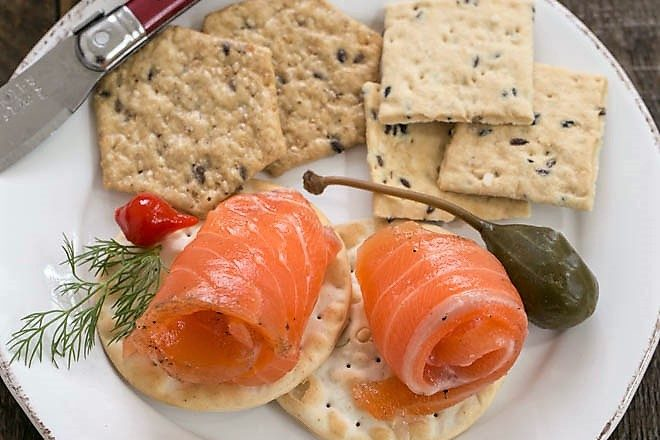 Gravlax on crackers on a small white plate with a red handle knife