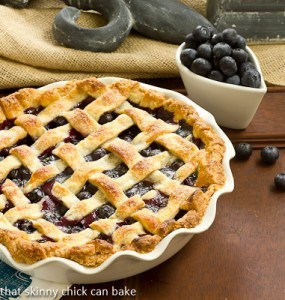 Lattice topped blueberry pie in a white ceramic pie plate with a bowl of blueberries