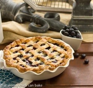 Lattice Topped Blueberry Pie in a ceramic pie plate next to a bowl of fresh blueberries