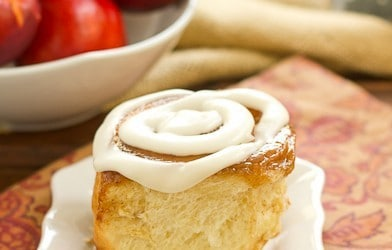 A nectarine cinnamon roll on a white plate over an orange pattern napkin