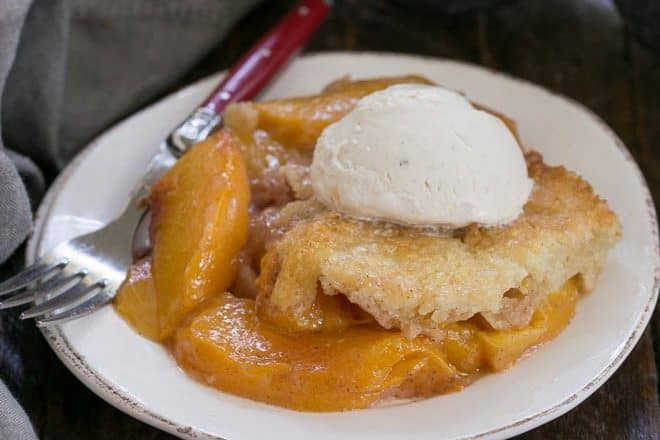 Peach Cobbler on a white dessert plate with a red handled fork