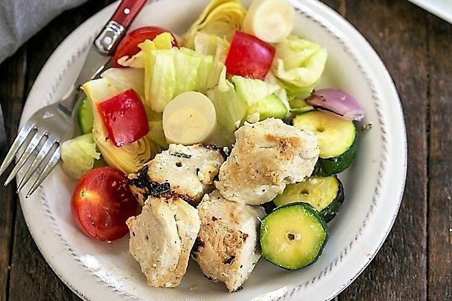 Overhead view of a white plate of grilled chicken kabobs and a green salad