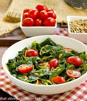 Massaged Kale Salad topped with tomatoes and seeds in a white bowl