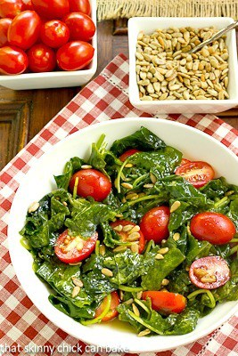 Massaged Kale Salad in a white bowl with toppings of seeds and tomatoes