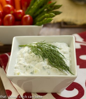 Tzatziki in a square white bowl with a sprig of dill