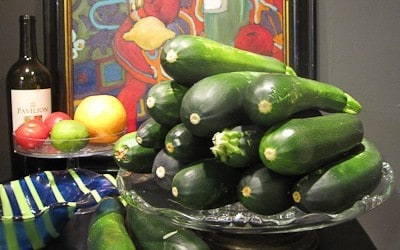 A bunch of zucchini in a silver bowl