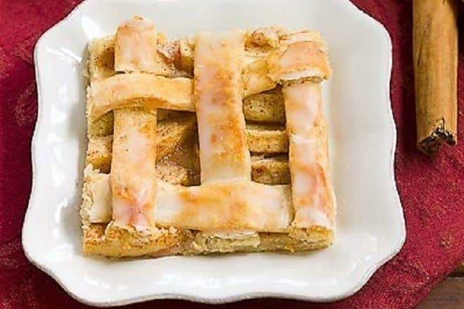 A slice of apple slab pie or apple squares on a white plate
