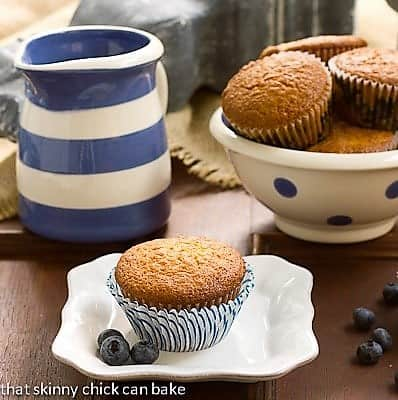 Sour Cream Blueberry Muffins in a polka dot ceramic bowl with one on a small white plate