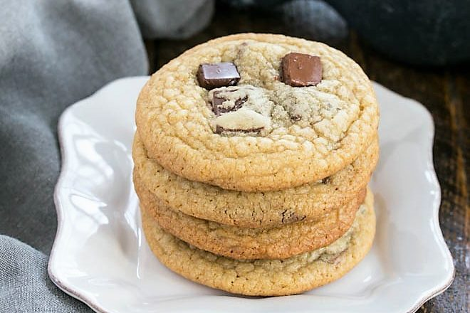4 brown sugar chocolate chunk cookies stacked on a square white plate