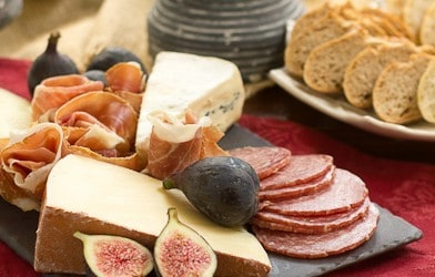 A simple cheese tray with cheeses, meats, and figs on a slate board