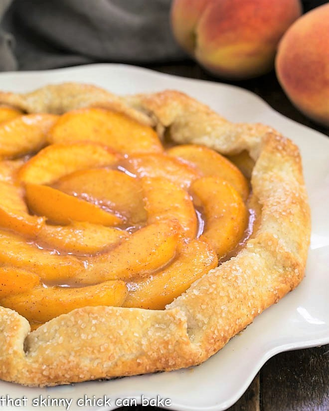 Partial closeup view of a peach galette on a white serving plate