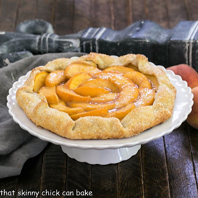 Peach galette on a white cake stand