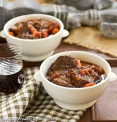 Two Bowls of Slow Cooked Beef Stew with Red Wine, Carrots and Tomatoes on a green checkered napkin