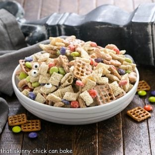 Side view of a shallow white bowl of Halloween Chex Mix