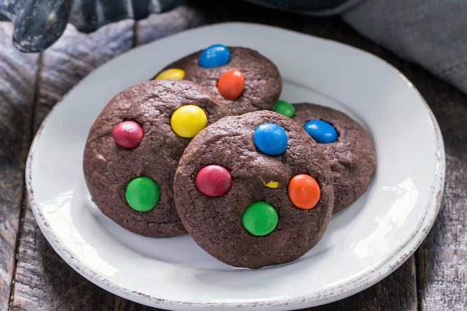 4 brownie cookies with M&Ms on a white dessert plate