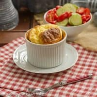 A muenster souffle in a ramekin with a bowl of salad over a red and white napkin
