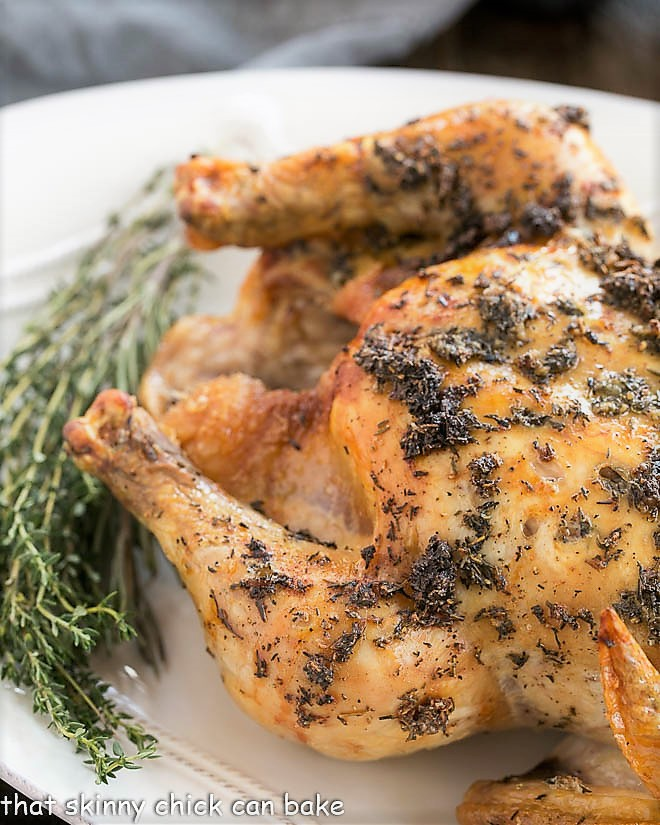 Whole Roasted Chicken on an oval platter garnished with thyme