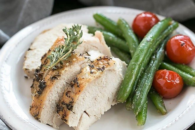 Whole roasted chicken on a white plate with green beans and tomatoes