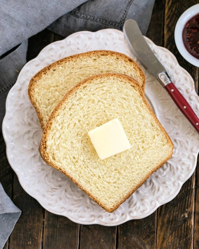 Two slices of potato bread with a pat of butter and a red handled knife on a decorative wite plate
