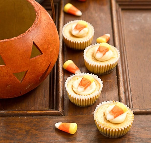 Mini Pumpkin Cheesecakes on a wooden panel next to a wooden jack-o-lantern