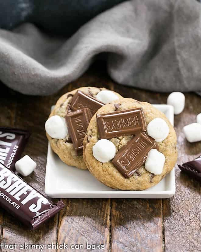 S'mookies AKA Gooey S'mores Cookies on a square white plate with mini Hershey bars