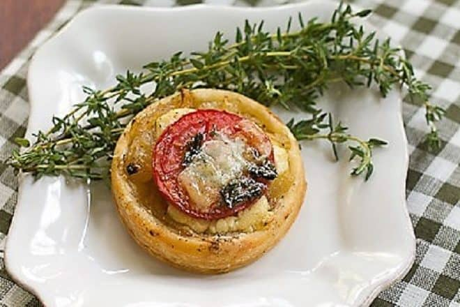 Tomato and Boursin Tartlet on a square white plate with fresh thyme