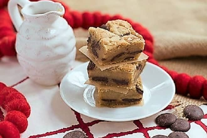 A stack of Caramel Chocolate Chip Cookie Bars on a white dessert plate