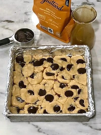 Unbaked caramel chocolate bars in a foil lined pan