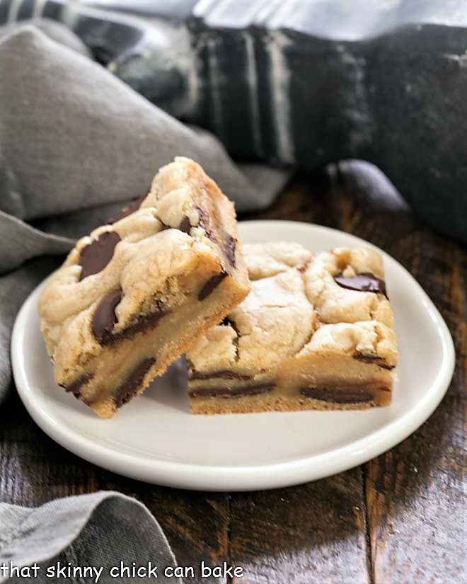 Two Caramel Chocolate Chip Cookie Bar on a small round white plate