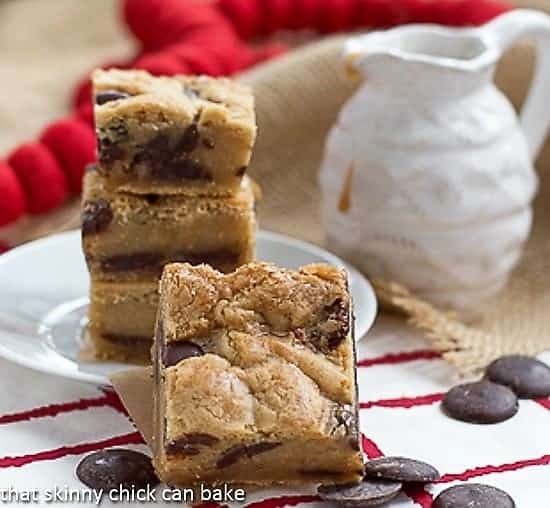 Caramel Chocolate Chip Bars by a small pitcher of caramel sauce