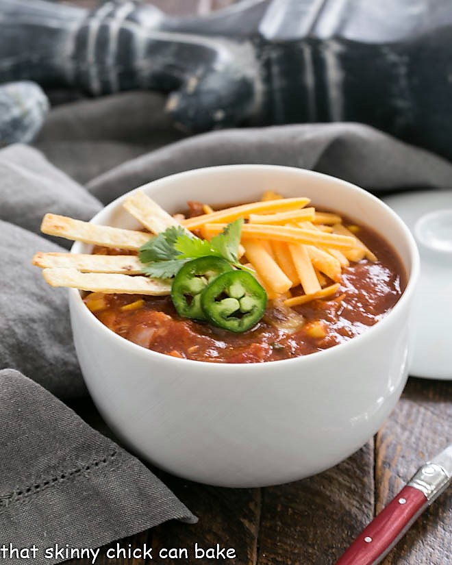 Side view of a white bowl filled with tortilla soup topped with garnishes