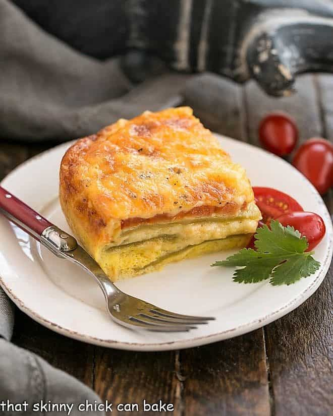 Chili Relleno Casserole slice on a round white place with a red handled fork