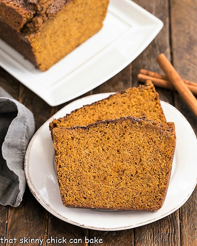Slices of pumpkin bread on around white plate next to cinnamon sticks