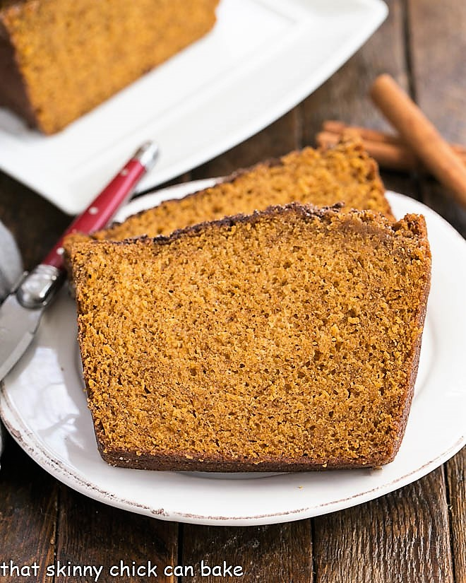 Two slices of cinnamon topped pumpkin bread on a white plate