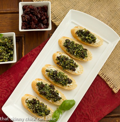 Overhead view of Cranberry Pesto Goat Cheese Crostini on a white ceramic tray