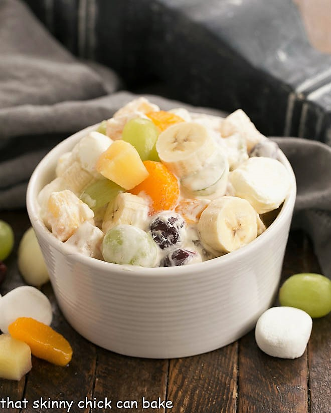 24 hour fruit salad in a white bowl garnished with fruit and marshmallows