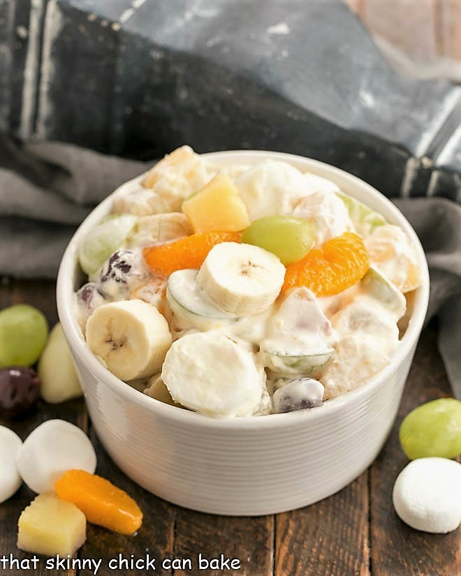 Holiday Fruit Salad with Marshmallows in a white ceramic bowl surrounded by fruit and marshmallows