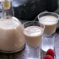 Irish cream recipe in a carafe and two shot glasses of Baileys with some fresh raspberries
