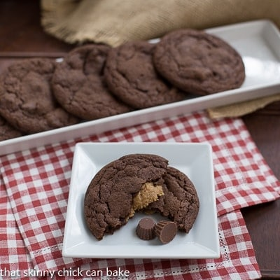 Peanut Butter Stuffed Chocolate Cookies on a white tray with one broken open on a small white plate