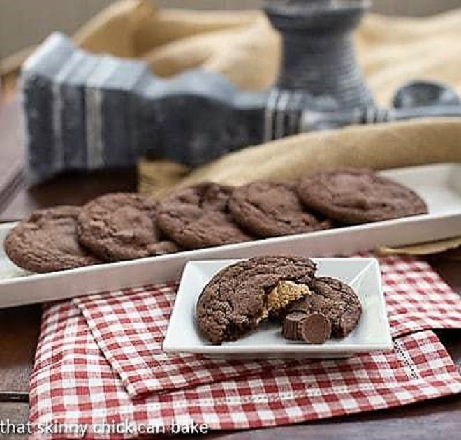 Peanut Butter Stuffed Chocolate Cookies on a rimmed tray and on a square white plate