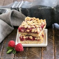Two raspberry bars stacked on a square white plate with fresh raspberries and mint to garnish